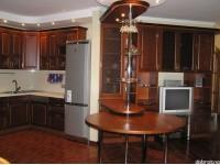 """Кухня - kit_0018 - Великолепная кухня студия в классическом стиле. Фасады выполнены из массива дерева (бук) тонированного под итальянский орех. Барная стойка скомбинирована с круглым деревянным столом, вращающимся вокруг трубы Pole-System.<br>Для расчета цены подобной кухни укажите код этой кухни в заявке в графе """"Доп. информация"""" <a class=""""kuhni-foto-link"""" title=""""Расчет кухни онлайн"""" href=""""http://dobrotno.com.ua/zakazat-dizayn-kuhni"""" target=""""_blank""""> Рассчитать кухню</a>"""